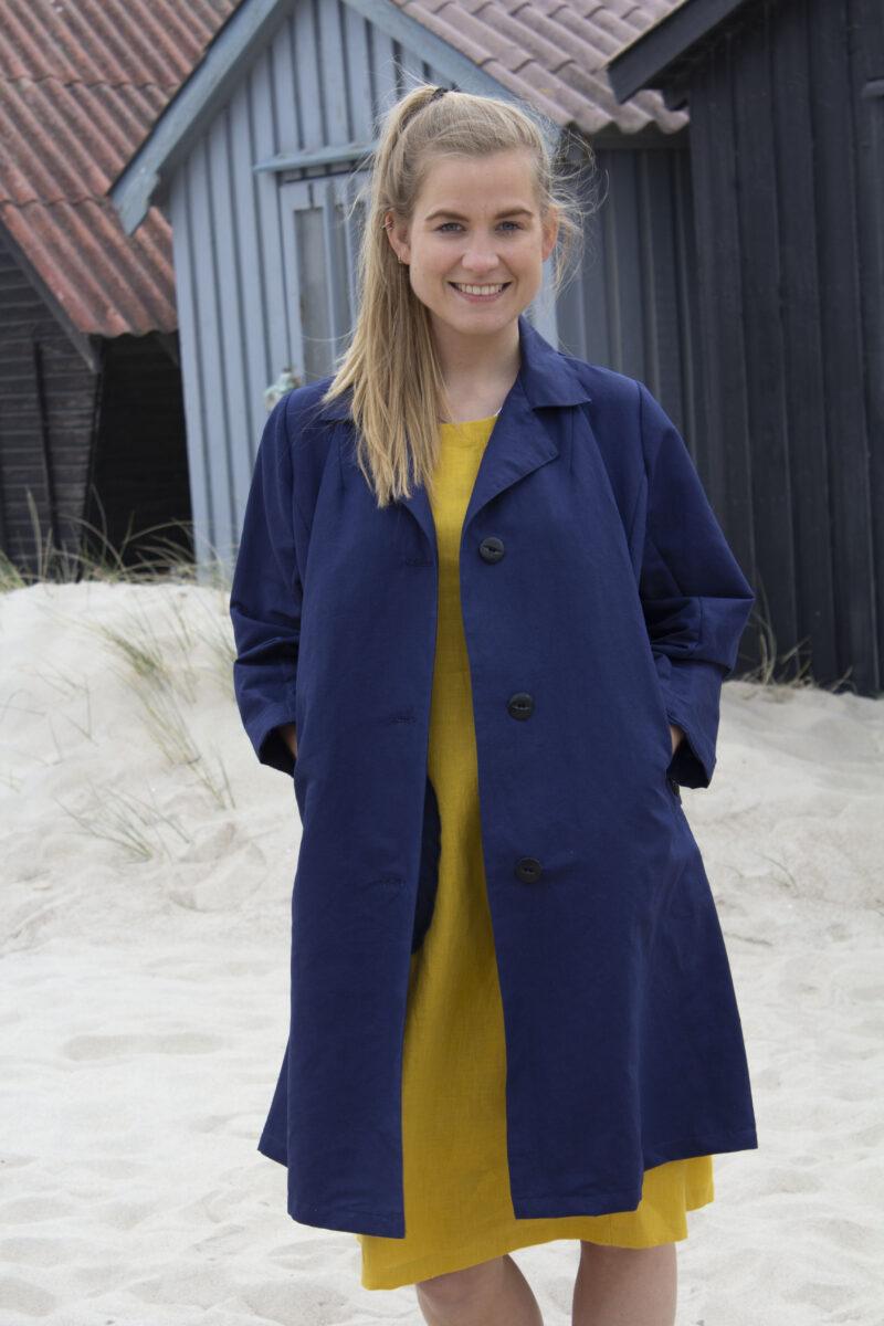 Kvinde i gul hørkjole og blå jakke
