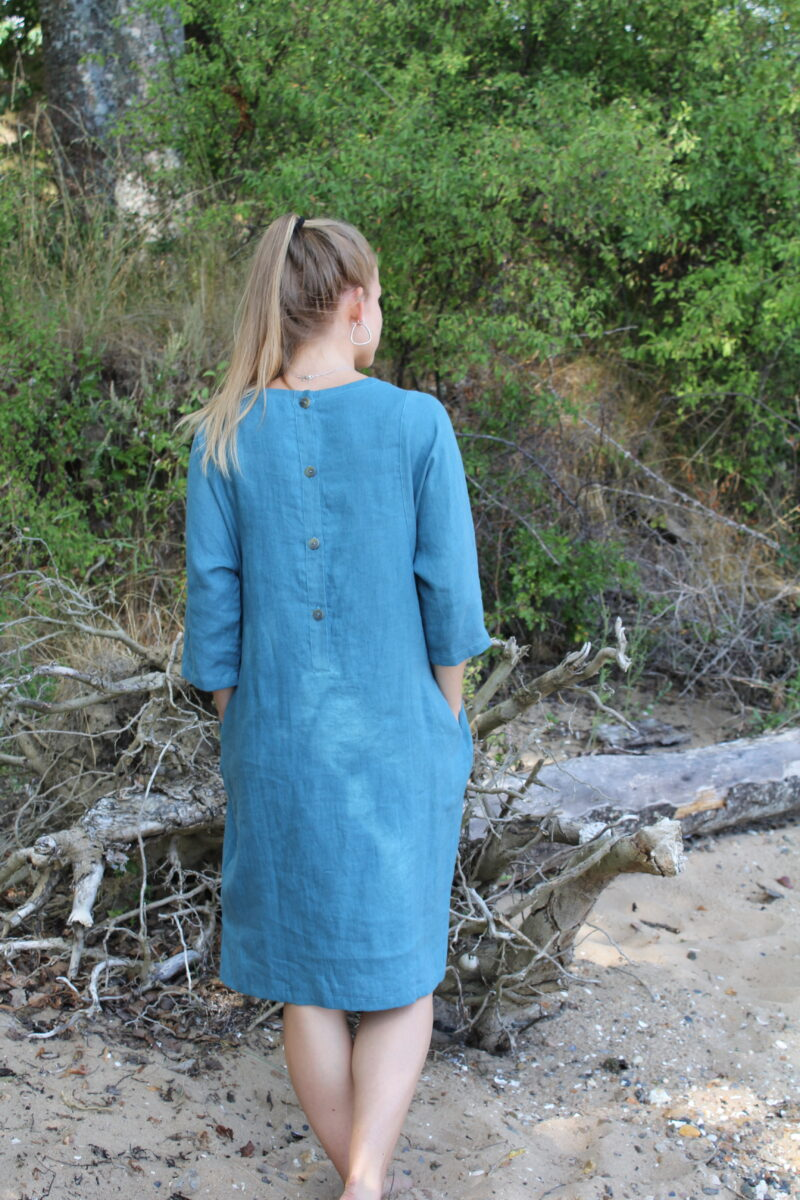 Woman from the back in blue linen dress with buttons