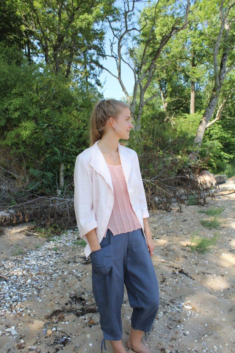 Kvinde i lyserød hørjakke og grå hørbukser