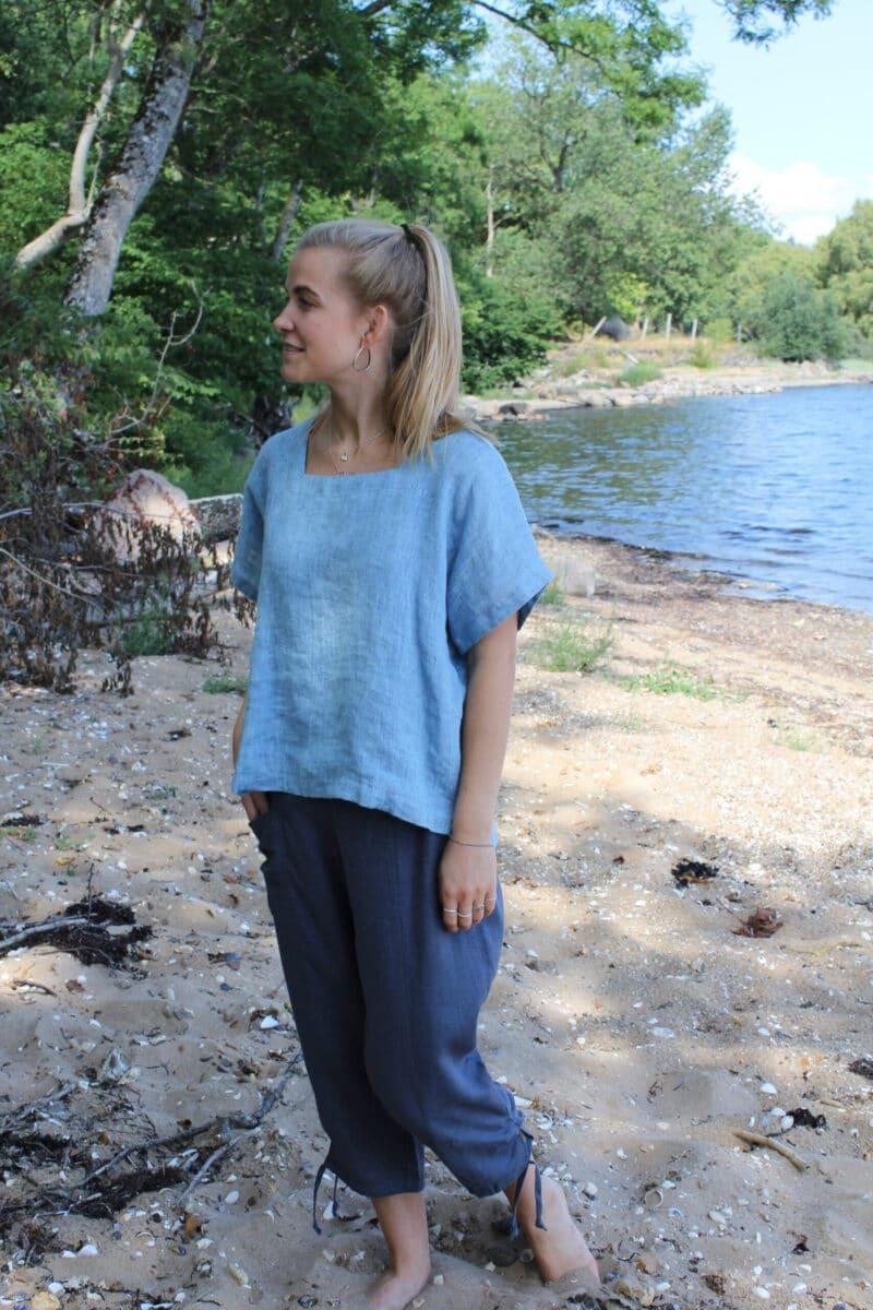 Kvinde i melange blå hør top og gråblå bukser