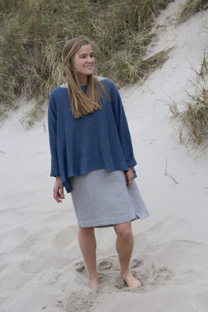 Woman in striped linen dress and blue knitted linen blouse