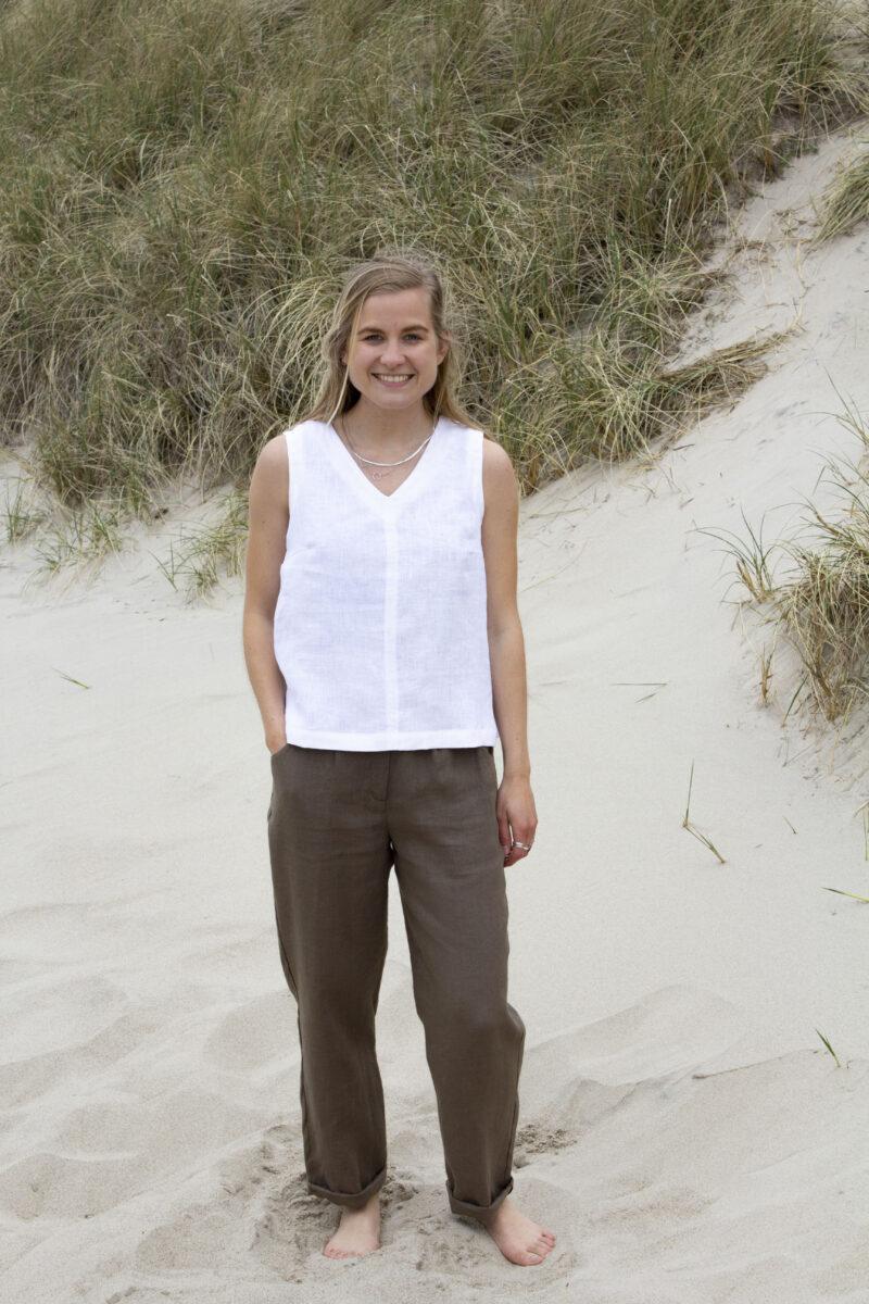 Kvinde i hvid hørtop uden ærmer og brune hørbukser