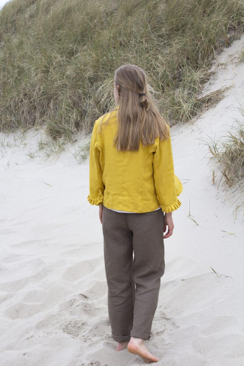 Kvinde i brune hørbukser og gul hørjakke