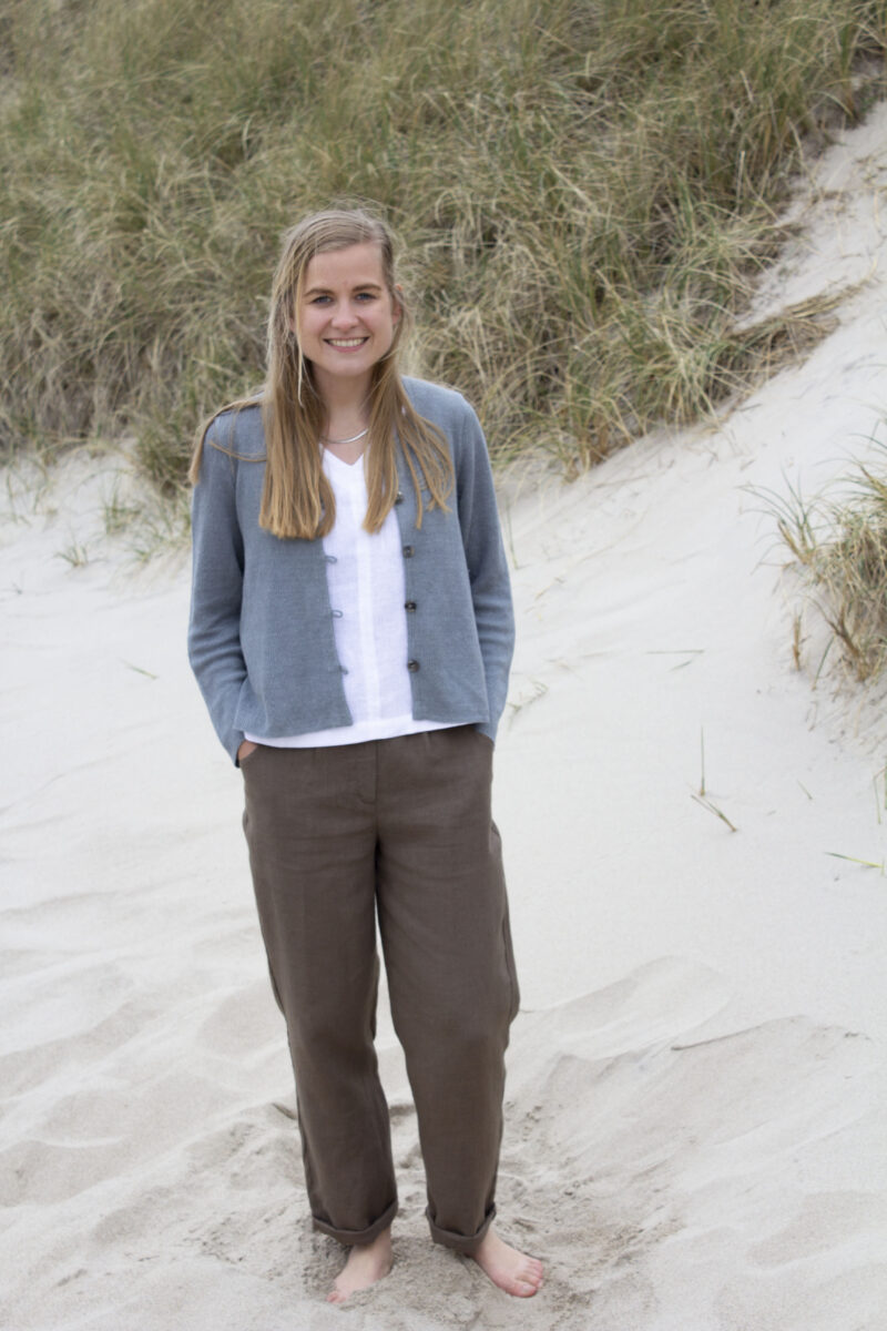 Woman in brown linen pants, white top, and knitted cardigan