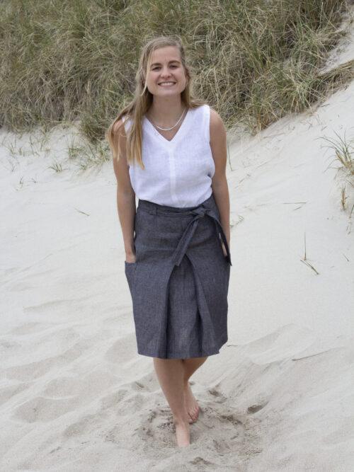 kvinde i hvid hør top og grå hør nederdel