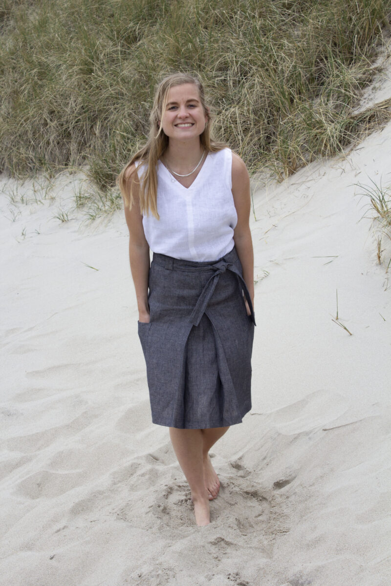 Woman in white linen top and grey linen skirt