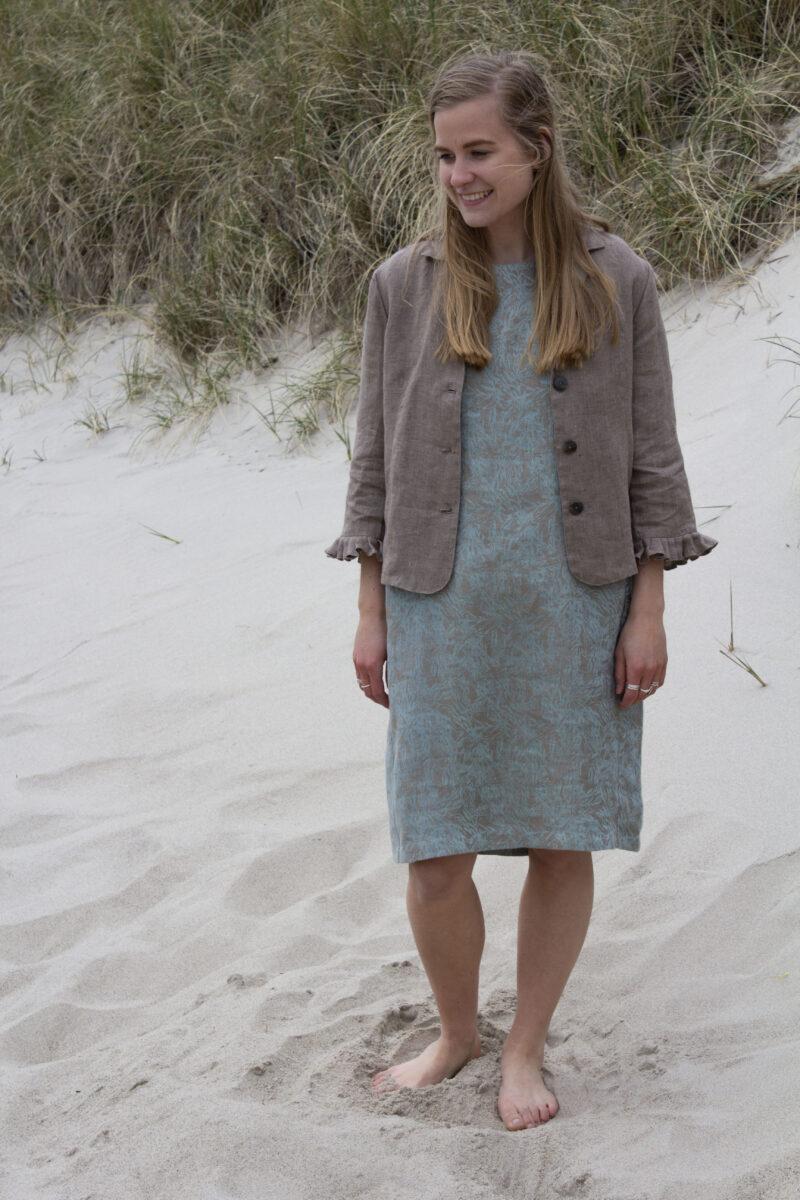 Kvinde med mønstret hørkjole og sandfarvet hørjakke