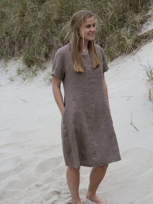 Kvinde i sandfarvet hørkjole