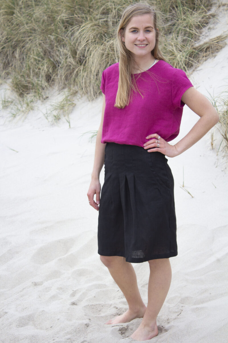 Woman in cherise linen top and black linen skirt
