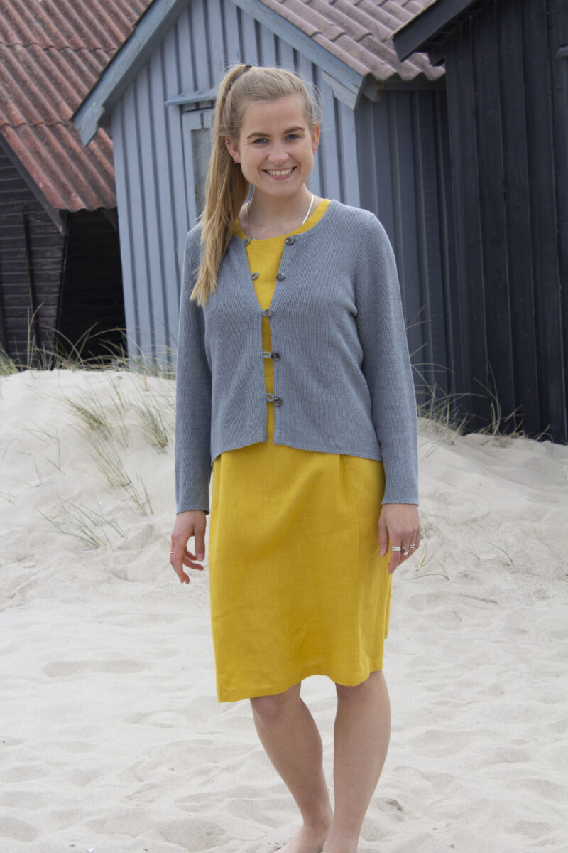 Woman wearing a yellow dress and knitted linen cardigan in grey