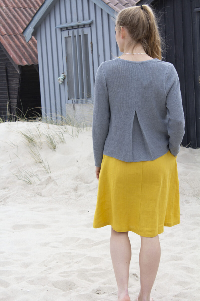 Woman from the back wearing a yellow dress and knitted linen cardigan in grey