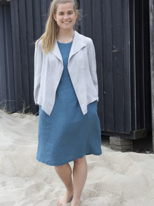 Woman wearing a blue linen dress and grey linen jacket