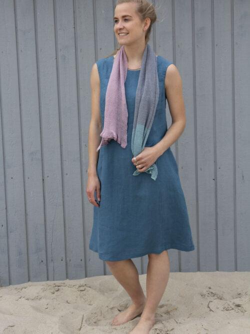 Kvinde i blå hør sommerkjole og med et hørtørklæde