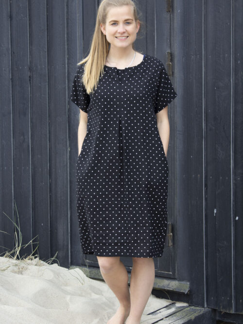 Kvinde i sort hørkjole med hvide prikker