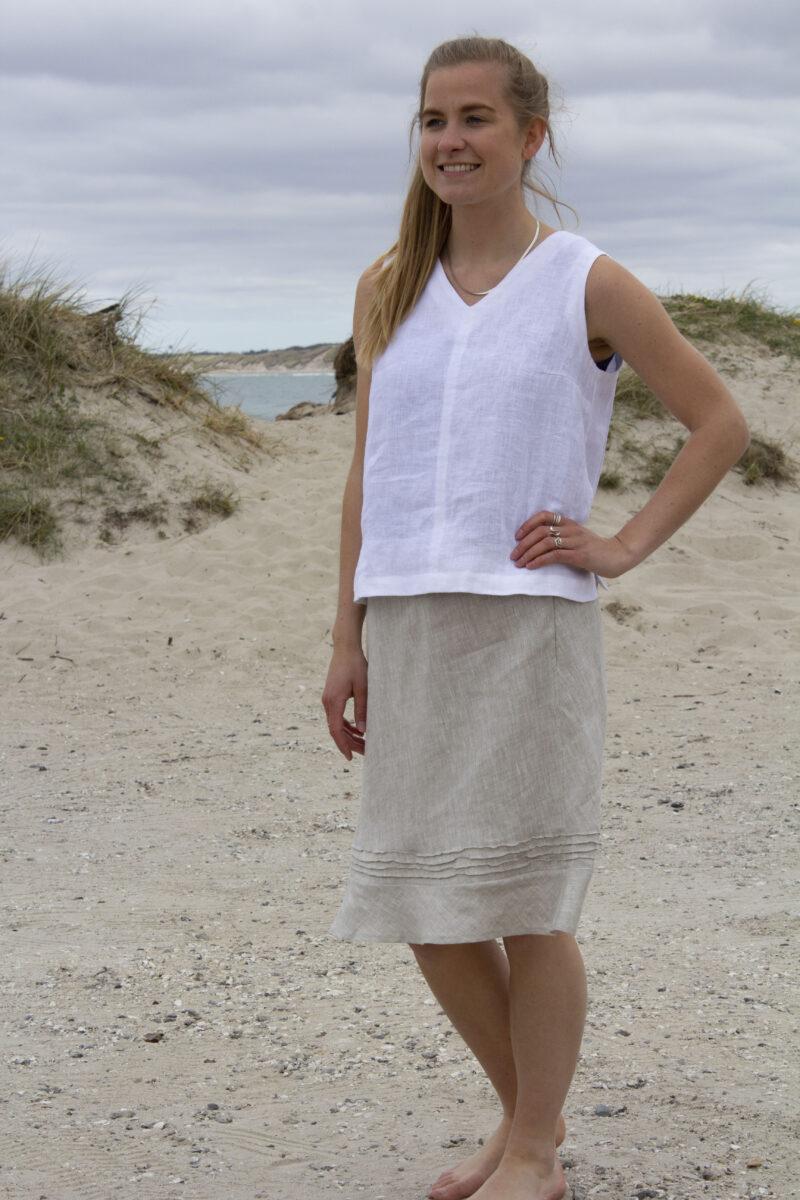 Kvinde i hvid hørtop uden ærmer og natur farvet nederdel