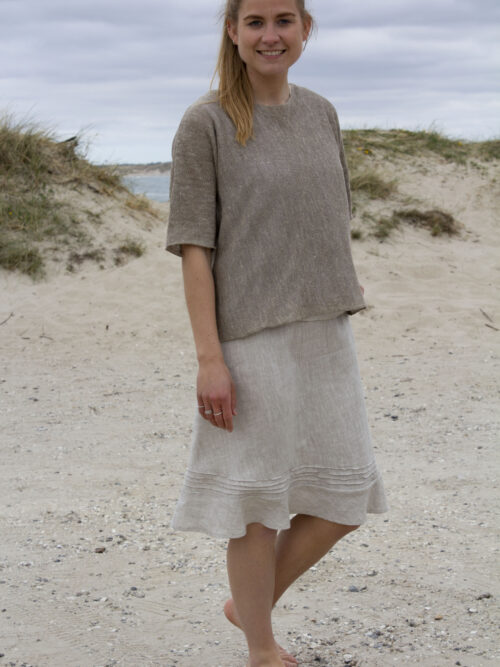 Woman in knitted top and melange linen skirt