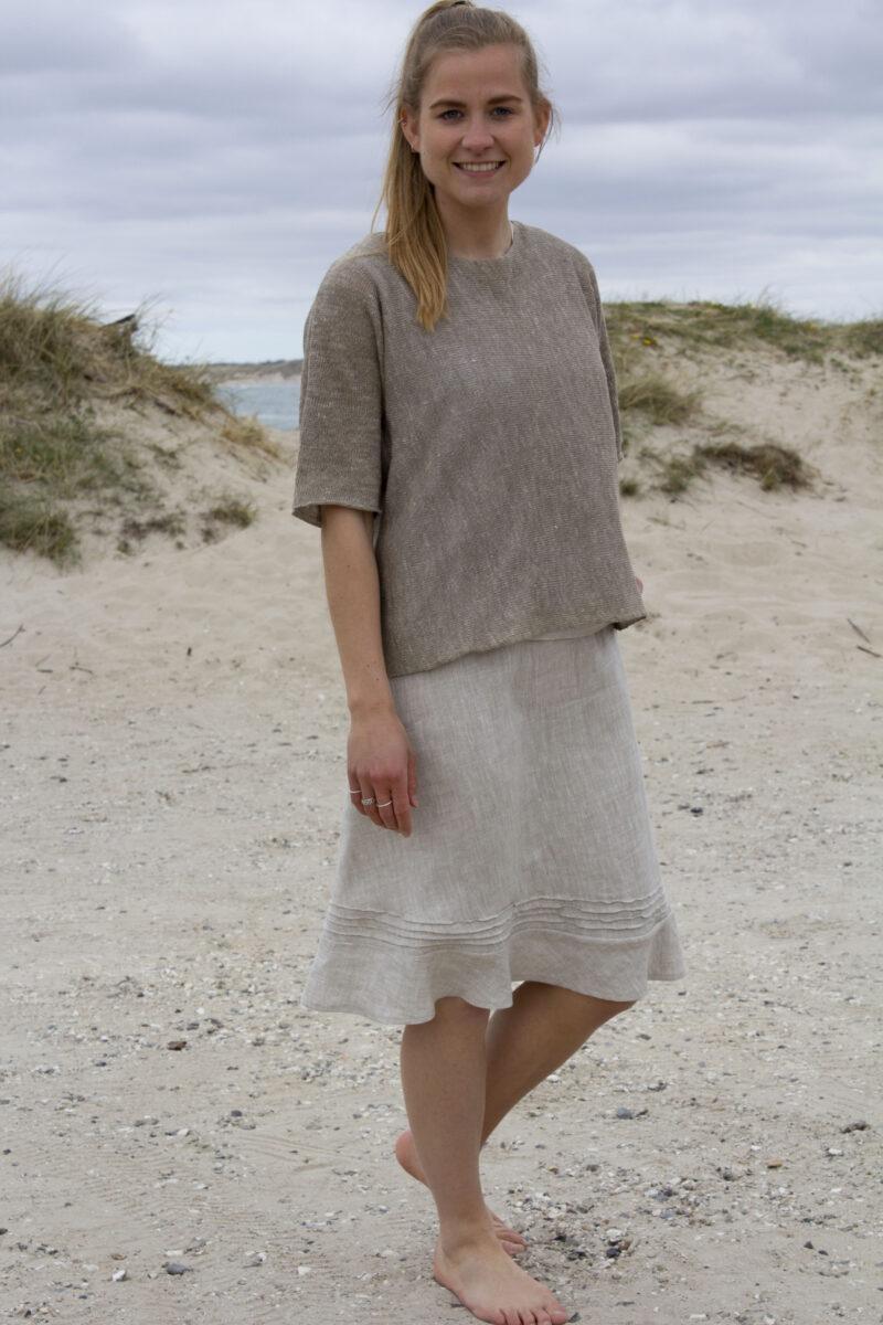Kvinde i strikket hørtop og melange natur hørnederdel