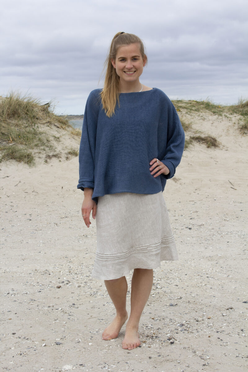 Woman in blue knitted blouse and melange linen skirt