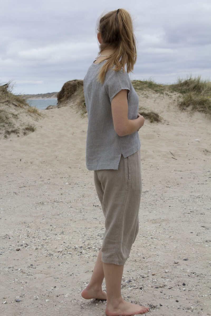 Woman from the side in striped linen top and natural linen pants