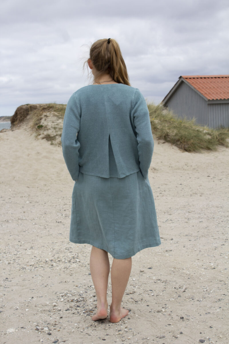 Woman from the back in green linen dress with matching linen cardigan
