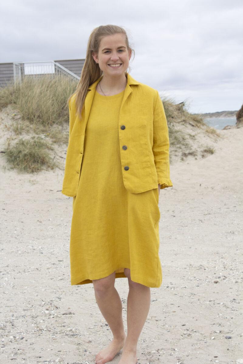 Kvinde i gul hørkjole og gul hørjakke