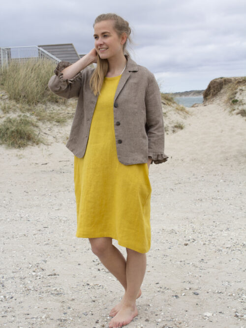 Woman in yellow dress and linen jacket
