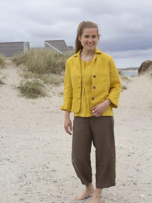 Kvinde i brune hørbukser, gul hørtop og gul hørjakke