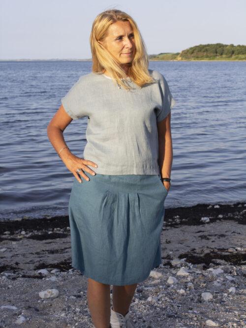 woman in green linen top and blue linen skirt