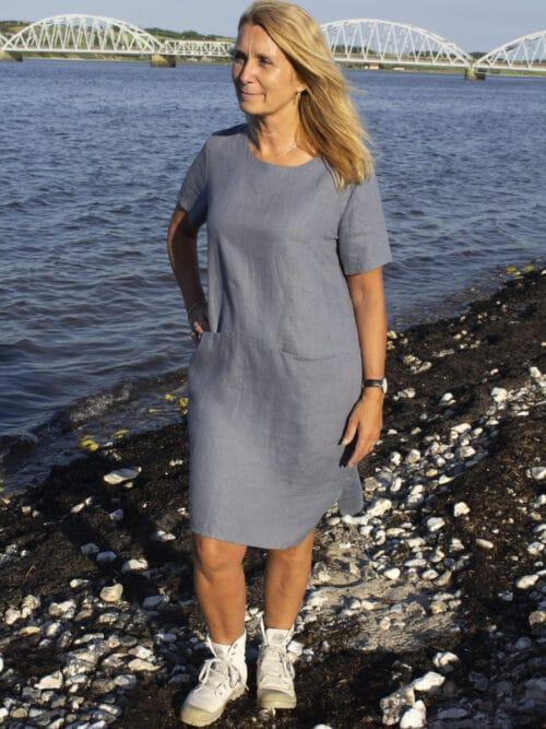 kvinde i grå hørkjole med lommer foan